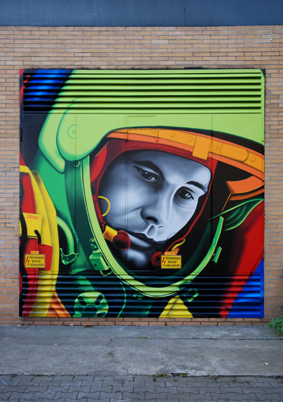 SiveOne and Mr. Flash painted on the subject of technology, research and science a pop art portrait of Juri Gagarin during 11.11.2011. Gagarin was the first cosmonaut of the humanity. He has circuited the earth in space fifty years ago. The graffiti art of 3Steps is to be found on a building at the THM university campus in Giessen.
